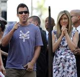 Actress Jennifer Aniston stands next to actor Adam Sandler before unveiling her star on the Walk of Fame in Hollywood, California February 22, 2012. REUTERS/Mario Anzuoni
