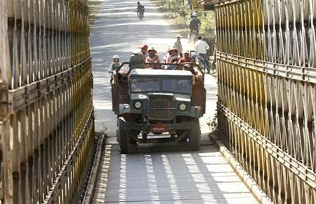 Labourers from Myanmar sit on a truck loaded with bricks as they cross the Indo-Myanmar border bridge at the border town of Moreh, in Manipur, February 3, 2012. REUTERS/Rupak De Chowdhuri/Files