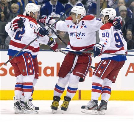 Washington Capitals Alex Ovechkin (C) and Marcus Johansson (R) celebrate a goal scored by Keith Aucoin (L) in the second period of their NHL hockey game against Toronto Maple Leafs in Toronto February 25, 2012.   REUTERS/Fred Thornhill