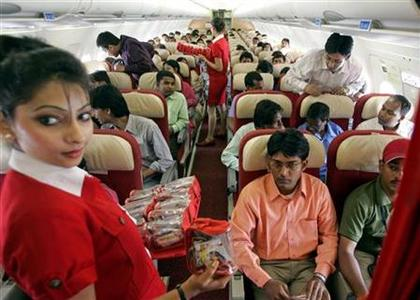 Stewardesses serve passengers inside a Kingfisher Airlines aircraft in the skies over New Delhi May 21, 2006. REUTERS/Kamal Kishore/Files