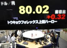 Foreign exchange dealers are seen beneath an electronic board displaying the Japanese Yen's exchange rate against the U.S. dollar at a foreign exchange trading company in Tokyo February 22, 2012. REUTERS/Kim Kyung-Hoon