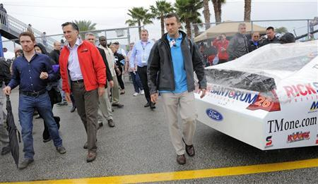 Republican presidential candidate and former Massachusetts Governor Mitt Romney (2nd L) walks past the number 26 Ford, driven by Tony Raines, with advertising for Romney's opponent, Rick Santorum, during his appearance at the NASCAR Sprint Cup Series 54th Daytona 500 race at the Daytona International Speedway in Daytona Beach, Florida, February 26, 2012. REUTERS/Brian Blanco
