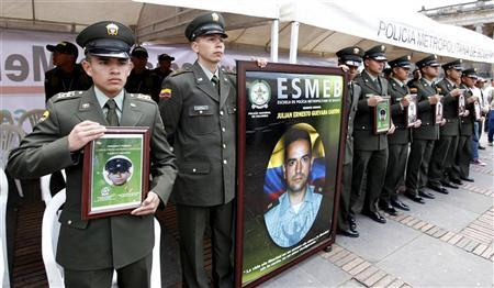 Colombian policemen show portraits of their comrades, who were kidnapped by FARC rebels, during a protest against kidnappings at Bolivar Central square in Bogota, February 23, 2012. REUTERS/Jose Miguel Gomez