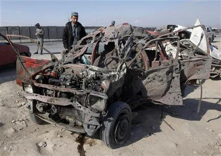 An Afghan policeman inspects a wreckage of a car hit by a car bomb attack in Jalalabad province February 27, 2012. REUTERS/Parwiz