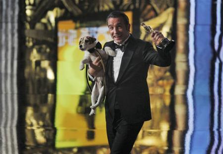 Best actor winner Jean Dujardin of France carries Uggie the dog after ''The Artist'' won the Oscar for Best Picture at the 84th Academy Awards in Hollywood, California, February 26, 2012.  REUTERS/Gary Hershorn