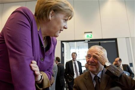 German Chancellor and head of the Christian Democratic Union (CDU) Angela Merkel (L) talks with Finance Minister Wolfgang Schaeuble before a special meeting of the CDU parliamentary faction in Berlin on the parliamentary vote on financial aid for Greece, February 27, 2012.  Germany's parliament was almost certain to endorse a second Greek bailout on Monday but Chancellor Angela Merkel was torn between domestic pressure to stop throwing good money after bad and global calls to boost Europe's crisis defences.  REUTERS/Thomas Peter (GERMANY - Tags: POLITICS BUSINESS)