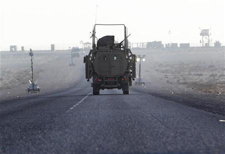 The last U.S. Army convoy vehicle drives down the road after crossing into Kuwait from Iraq December 18, 2011. The last convoy of U.S. soldiers pulled out of Iraq on Sunday, ending nearly nine years of war that cost almost 4,500 American and tens of thousands of Iraqi lives and left a country still grappling with political uncertainty.   REUTERS/Shannon Stapleton