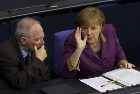 German Chancellor Angela Merkel (R) talks with Finance Minister Wolfgang Schaeuble during a debate before a parliamentary vote on a Greek bailout package in the Bundestag, the lower house of parliament, in Berlin , February 27, 2012.  REUTERS/Thomas Peter