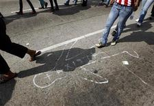People walk past a chalk outline drawn on the pavement to represent a dead body during a march against violence in Acapulco October 19, 2011. This city of dazzling hotels and sunlit beaches rose to fame as a playground of Hollywood stars. Today, Acapulco has now earned a very different reputation-for gangland decapitations, kidnappings and extortion.    REUTERS/Tomas Bravo