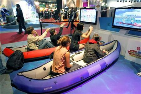 Visitors play a rowing race with Wii games during a visit at the Paris Games Week show in Paris October 21, 2011. REUTERS/Charles Platiau/Files