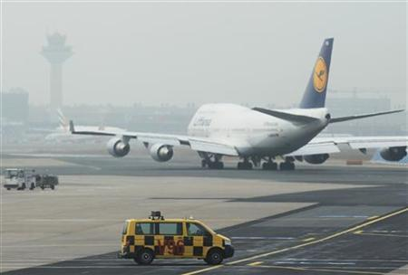 An airport apron controller vehicle is pictured next to a Lufthansa Boeing B747-400 aircraft on the runway at Frankfurt's airport February 27, 2012. REUTERS/Alex Domanski (GERMANY - Tags: BUSINESS TRANSPORT EMPLOYMENT)