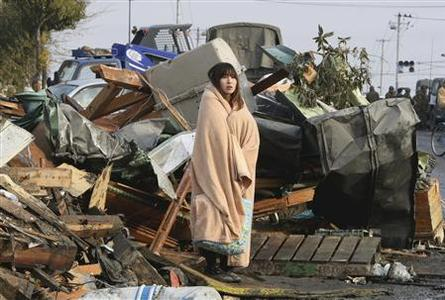 Yuko Sugimoto, wrapped in a blanket, stands in front of a pile of debris caused by the March 11 earthquake and tsunami in Ishinomaki, Miyagi Prefecture, northern Japan in this file photo taken by Yomiuri Shimbun on March 13, 2011. REUTERS/Yomiuri Shimbun