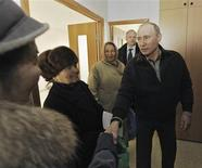Russian Prime Minister Vladimir Putin (R) shakes hands with local residents as he observes apartments granted for residents of a damaged nine-storey building, a section of which collapsed after a household gas explosion, in the southern city of Astrakhan February 28, 2012.  REUTERS/Yana Lapikova/RIA Novosti/Pool