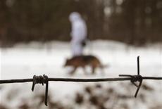 Белорусский пограничник с собакой патрулирует границу с Польшей 23 февраля 2012. Белоруссия во вторник предложила покинуть страну послу Польши и главе представительства Евросоюза в ответ на санкции, которые ЕС ввел накануне против двух десятков белорусских судей и силовиков. REUTERS/Vasily Fedosenko