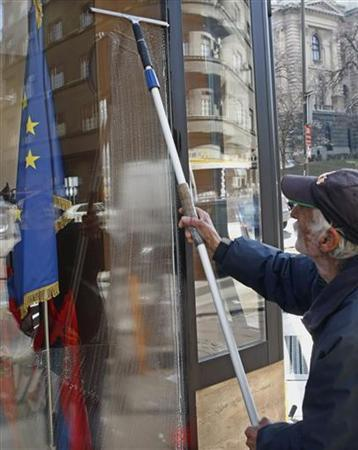 A European Union flag is seen behind a shop window being cleaned by a worker in Belgrade February 28, 2012. EU foreign ministers were discussing on Tuesday whether to recommend Serbia as an official candidate for the membership in the bloc , but a final decision could be taken at a summit of EU leaders on Thursday and Friday.  REUTERS/Ivan Milutinovic (SERBIA - Tags: SOCIETY POLITICS)