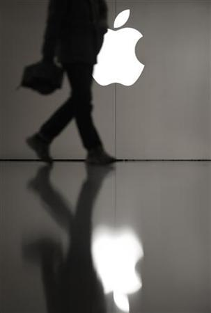 A man walks pass the Apple logo outside an Apple store in Shanghai February 28, 2012. Yang Long-san, Apple's nemesis in a battle over the iPad trademark in China, once strutted the expo halls with dreams of market dominance. His company, Proview, may now be in ruins and his most valuable asset a disputed trademark, but those dreams remain intact. REUTERS/Carlos Barria (CHINA - Tags: BUSINESS LOGO)