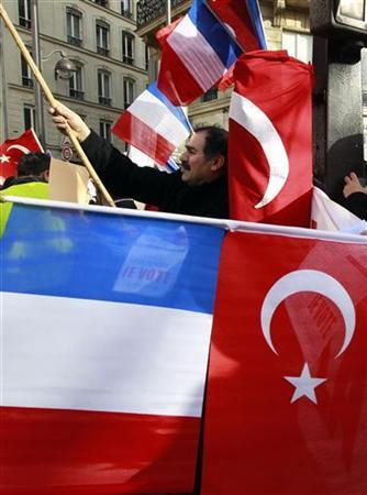 Franco-Turkish protesters hold a Turkish and French flags as they demonstrate near the Senate in Paris, January 23, 2012, ahead of a vote on a bill to make it illegal to deny the mass killing of Armenians by Ottoman Turks nearly a century ago was genocide, raising the prospect of a major diplomatic rift between two NATO allies. Lawmakers in the lower-house National Assembly voted overwhelmingly in December for the draft law outlawing genocide denial, prompting Ankara to cancel all economic, political and military meetings with Paris and recall its ambassador for consultations.   REUTERS/Pascal Rossignol (FRANCE  - Tags: POLITICS CIVIL UNREST)
