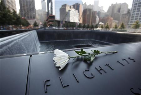 A single white flower is left on one of the panels containing the names of the victims of the attacks on the first day that the 9/11 Memorial was opened to the public at the World Trade Center site in New York, September 12, 2011.  REUTERS/Mike Segar