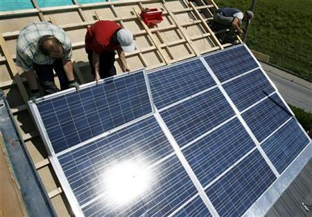 Employees of Solstis, a specialist solar roofing company, install photovoltaic tiles on a roof of a private house in Penthalaz, Southern Switzerland, August 21, 2008. REUTERS/Denis Balibouse
