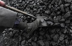 A coal merchant shovels coal at a coal yard in Melmerby, northern England November 5, 2008.