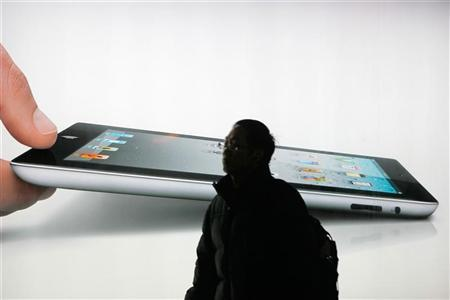 A man walks past an iPad 2 advertisement in Shanghai February 21, 2012. REUTERS/Aly Song