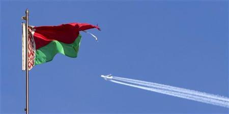 A plane flies in the sky in Minsk March 10, 2010. The Belarussian national flag is in the foreground. REUTERS/Vasily Fedosenko/Files