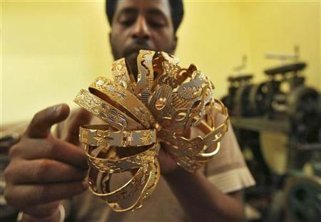 A worker counts gold bangles at a jewellery-making workshop in Jammu October 17, 2011. REUTERS/Mukesh Gupta/Files