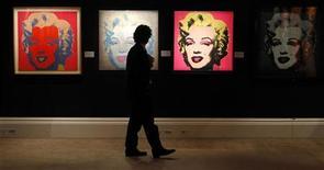 Работник аукционного дома Sotheby's проходит мимо портретов Мэрилин Монро, созданных художником Энди Уорхолом. Фотография сделана в Лондоне 13 сентября 2010 года. Мэрилин Монро выбрана символом Каннского фестиваля-2012 - таким образом организаторы отдали дань памяти актрисе в год пятидесятилетия ее смерти, говорится в сообщении устроителей, вышедшем во вторник. REUTERS/Suzanne Plunkett
