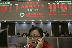 Трейдер работает в торговом зале Шанхайской биржи, 9 января 2008 года. Азиатские фондовые рынки выросли в среду в надежде на то, что новые дешевые кредиты Европейского Центробанка региональным банкам еще сильнее снимут напряжение на финансовых рынках и усилят аппетит к риску. REUTERS/Stringer