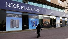 Женщина проходит мимо отделения банка Noor Islamic Bank в Дубае, 30 мая 2010 года. Дубайский банк Noor Islamic Bank под давлением США был вынужден прекратить свои деловые отношения с Ираном, что стало очередной экономической мерой Америки против Тегерана, разрабатывающего ядерную программу. REUTERS/Mosab Omar