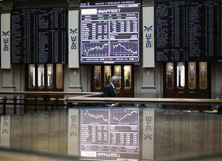 A man walks past screens at the bourse in Madrid November 7, 2011. REUTERS/Andrea Comas