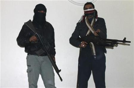 Two gunmen pose with their rifles in a secret house at Wadi khaled, near the Syrian border in northern Lebanon February 27, 2012. REUTERS/Roula Naimeh