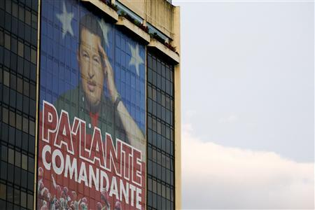 An image of Venezuelan President Hugo Chavez is seen in the windows of state oil company PDVSA headquarters building in Caracas February 28, 2012. The image reads, ''Go ahead, commander''. REUTERS/Jorge Silva