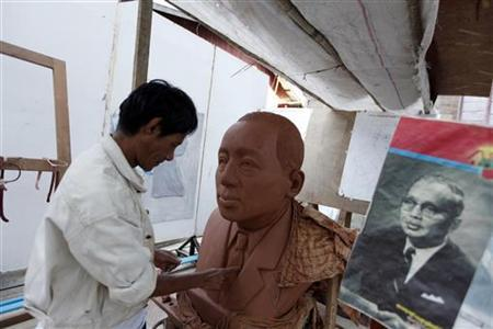 An artist works on a bust of former United Nations Secretary-General from Myanmar U Thant, while referring to a picture of him, at an art gallery in Yangon January 28, 2012. REUTERS/Soe Zeya Tun