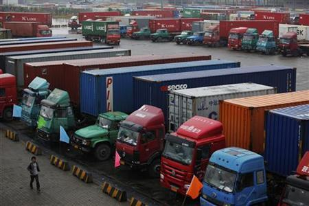 A man walks near trucks parked in a shipping container area at Shanghai Yangshan port December 7, 2011. REUTERS/Aly Song/Files