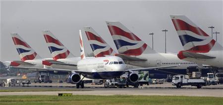 A British Airways passenger jet taxis past parked aircraft at Heathrow Airport, west of London May 25, 2010.  REUTERS/Eddie Keogh