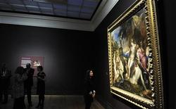 A staff member poses in front of Titian's painting 'Diana and Callisto' at the National Gallery in London, March 1, 2012.  REUTERS/Paul Hackett