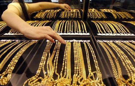 An employee arranges gold jewellery in the counter as her arm is reflected in the mirror at a gold shop in Wuhan, Hubei province August 25, 2011. REUTERS/Stringer