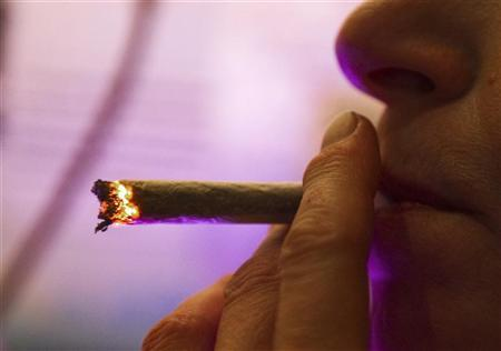 A Dutch woman smokes a cannabis cigarette in a coffee shop in Amsterdam October 6, 2011.  REUTERS/Toussaint Kluiters