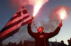 A firefighter raises flares as he protests in front of the parliament in Athens February 28, 2012.  REUTERS/John Kolesidis