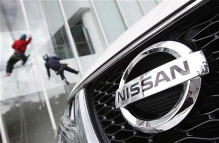 Workers clean windows next to a Nissan Motor Co.'s vehicle, displayed outside the company's showroom in Yokohama, south of Tokyo February 8, 2012. REUTERS/Yuriko Nakao/Files