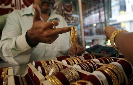 A shopkeeper shows gold bangles to a prospective buyer at a jewellery shop in Mumbai October 8, 2009. REUTERS/Arko Datta/Files