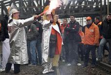 <p>Les sidérurgistes d'ArcelorMittal à Florange bloquent vendredi les entrées et sorties de la gare de triage qui alimente l'usine en réponse aux annonces de Nicolas Sarkozy et de leur direction concernant un redémarrage très hypothétique de leurs hauts-fourneaux, a constaté Reuters. /Photo prise le 2 mars 2012/REUTERS/Vincent Kessler</p>
