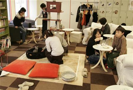 File photo of customers playing with cats at the Cat Cafe Calico in Western Tokyo, November 3, 2007. REUTERS/Michael Caronna