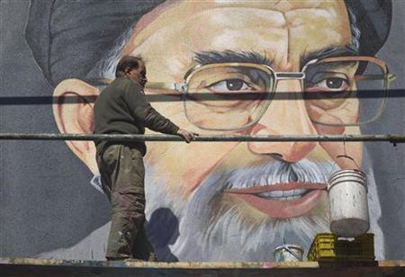 An Iranian worker rests in front of a huge portrait of Iran's Supreme Leader Ayatollah Ali Khamenei on a wall near a university during Friday prayers in Tehran, February 24, 2012. REUTERS/Morteza Nikoubazl