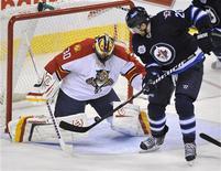 """Игрок """"Виннипега"""" Блэйк Уиллер (справа) забрасывает шайбу в ворота Скотта Клемменсена из """"Флориды"""" в матче НХЛ в Виннипеге 1 марта 2012 года. """"Виннипег"""" сократил отставание от лидирующей в Юго-восточном дивизионе """"Флориды"""", дома разгромив """"пантер"""" со счетом 7-0 в матче регулярного чемпионата НХЛ в четверг вечером. REUTERS/Fred Greenslade"""