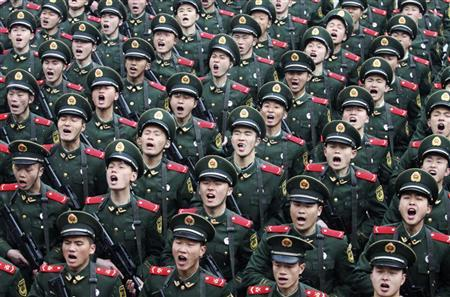 Recruits of the People's Liberation Army (PLA) shout slogans during a handover ceremony on a rainy day at a military base in Hangzhou, Zhejiang province February 10, 2012. REUTERS/Stringer