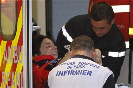 French journalist Edith Bouvier (L) is loaded onto an ambulance on a stretcher after her arrival on a government plane at Villacoublay military airport near Paris March 2, 2012. REUTERS/Charles Platiau