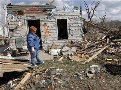 Janet Clark looks over what is left of her storm damaged home after a tornados hit in Henryville, Indiana March 3, 2012. Clark was able to survive the tornado strike by hiding in the bathroom of her home. The latest in a series of powerful tornadoes raked across a broad swath of the U.S. Midwest and Southeast, killing at least 33 people in four states, authorities said on Saturday.  REUTERS/ John Sommers II