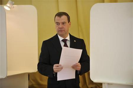 Russian President Dmitry Medvedev walks to cast his vote in a polling station in Moscow March 4, 2012. REUTERS/Kirill Kudryavtsev/Pool